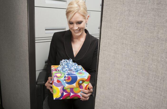 Glad kvinde med gave i hænderne